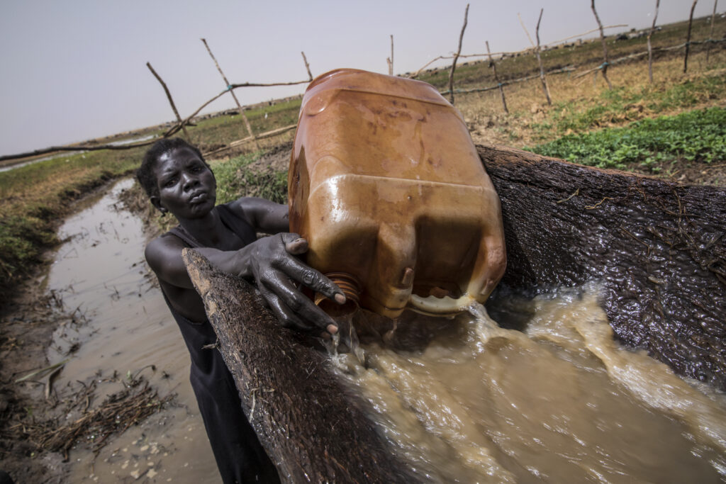 A woman irrigates her garden in South Sudan