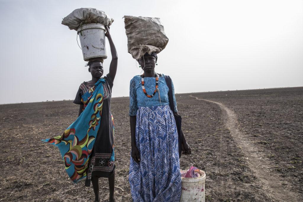 Two women carry crops across a dry field