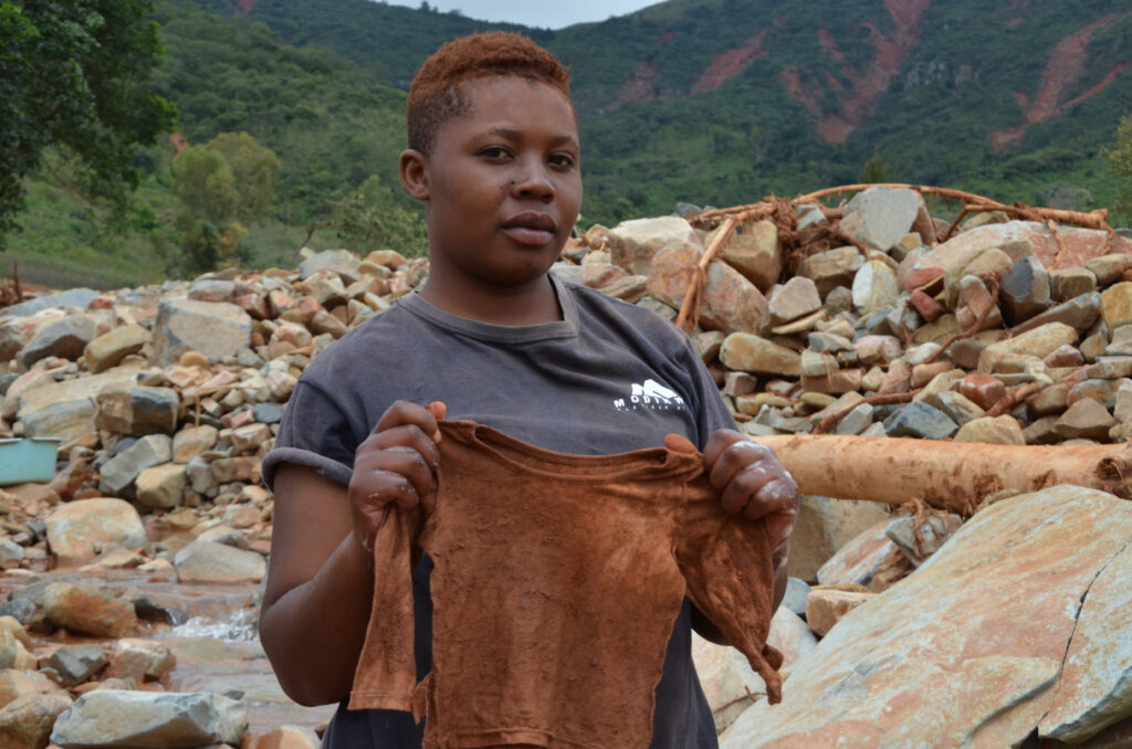 A woman holds up her deceased daughter's shirt following a landslide