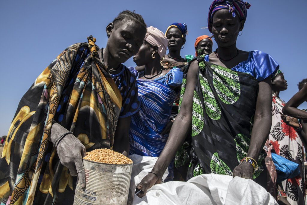 A group of women lean over bags of food.