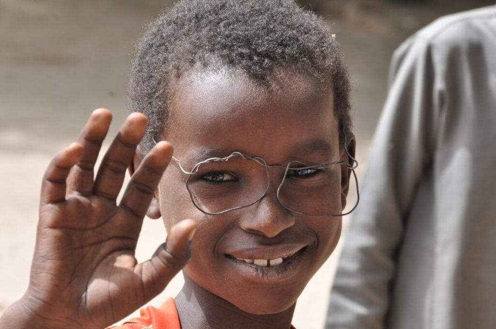 A boy waves at the camera, wearing handmade toy glasses.
