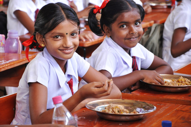 Two young schoolgirls eat a meal at a table.