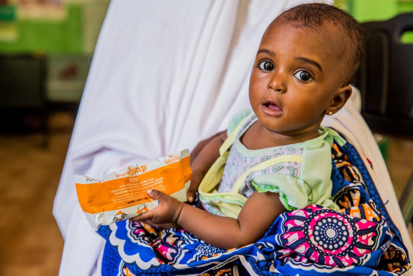 little girl holding peanut bar in mother's lap
