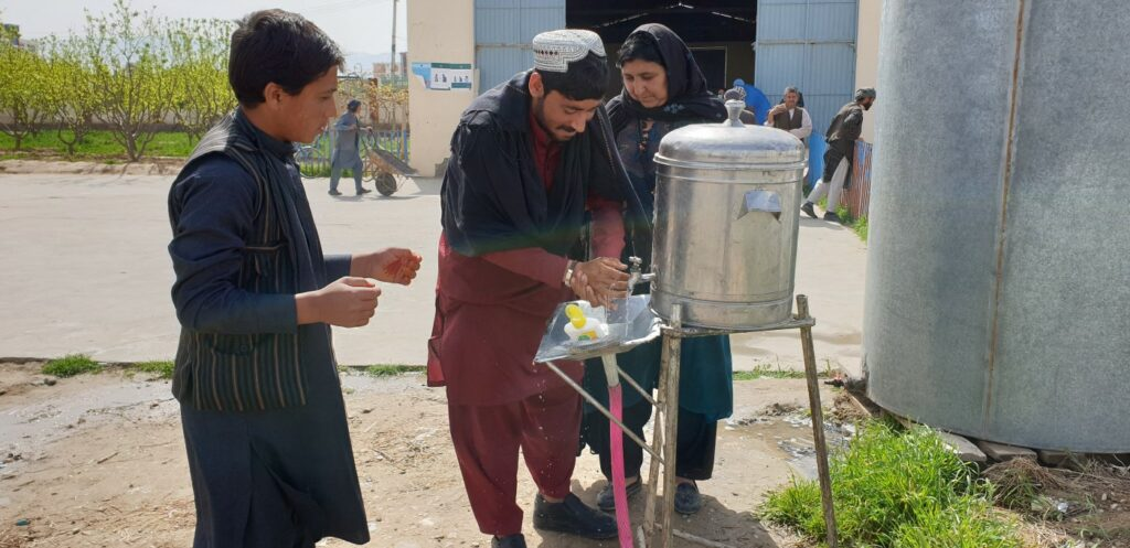 Three Afghans wash their hands at a sanitizing station outside a food distribution center.