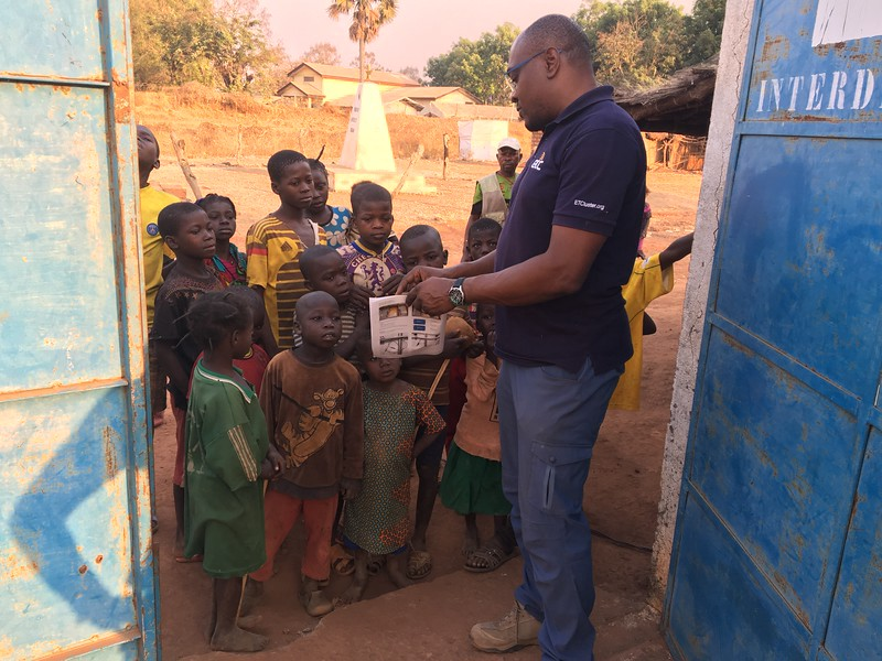 Sylvain Tiako shows a diagram on paper to a group of children