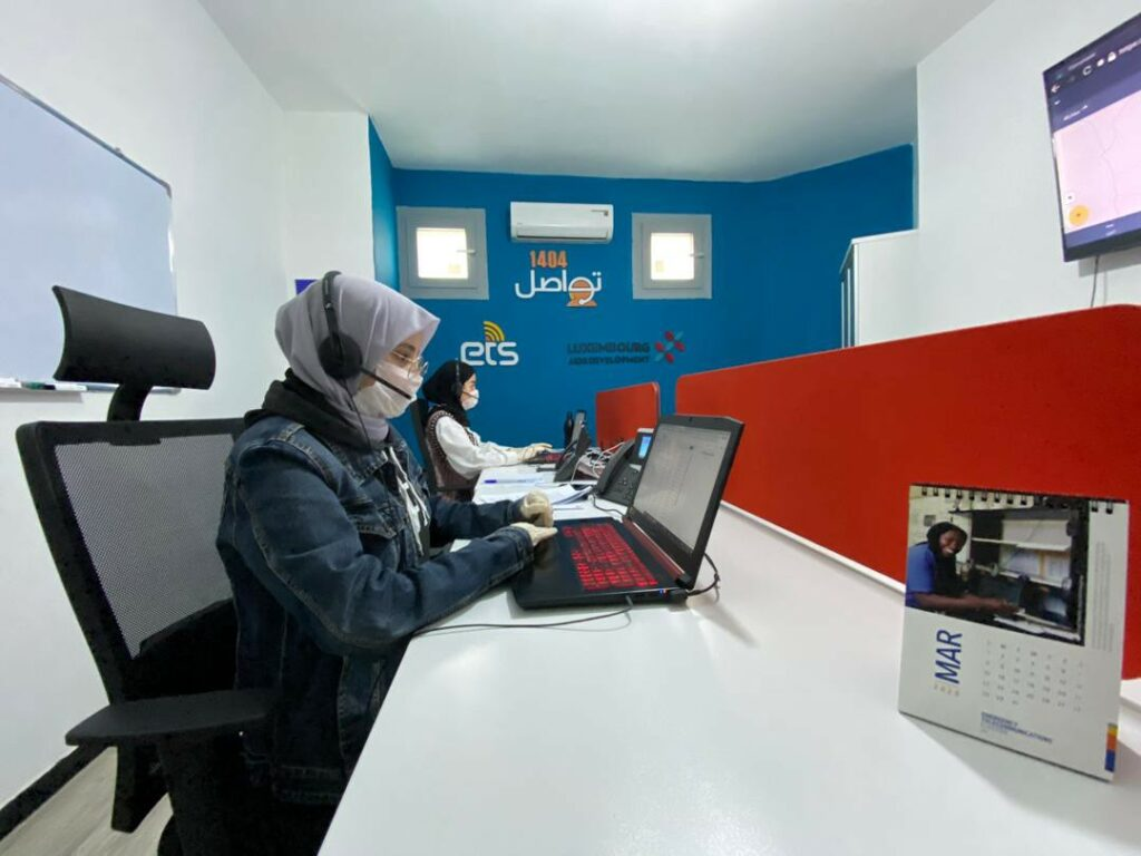 Two women in hijab and medical masks work at laptops in a call center