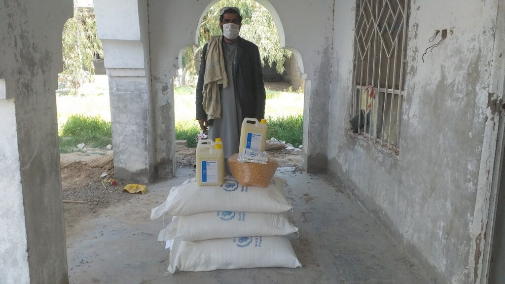 Obaidullah, a farmer wearing a mask, stands in front of a pile of food rations.