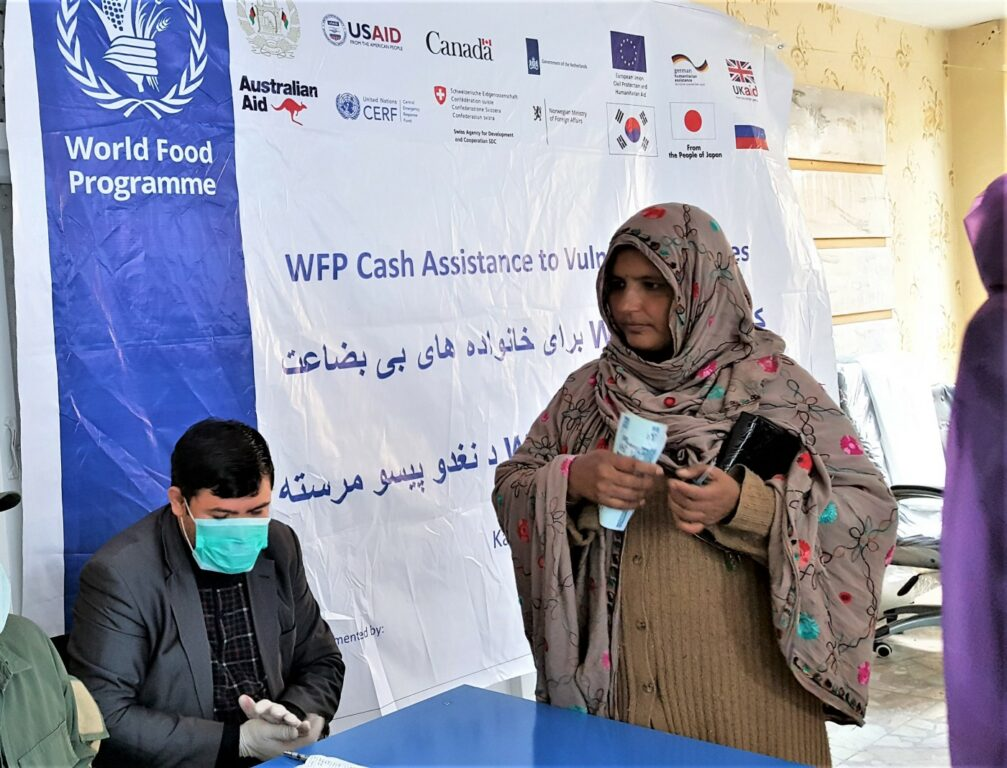 A WFP worker in a mask registers a standing woman for cash assistance.