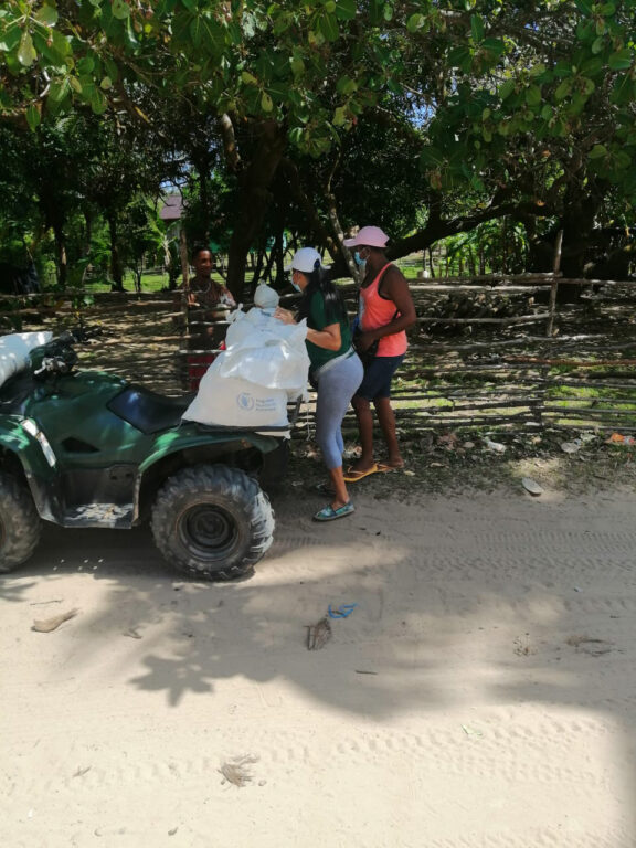 Two teachers unload food from an ATV