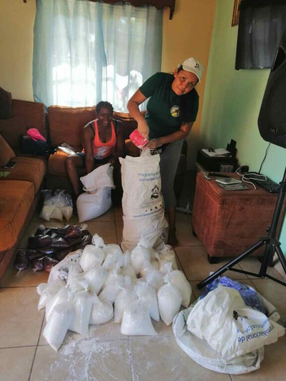 A teacher unloads a food delivery in a family living room