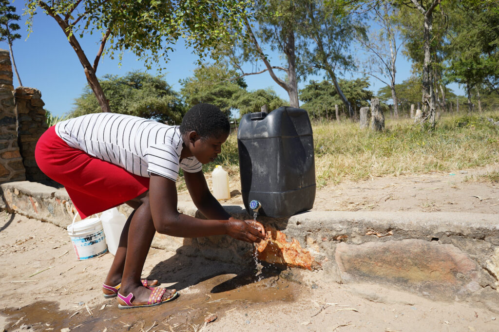 A woman washes her hands at a at a hand washing station.