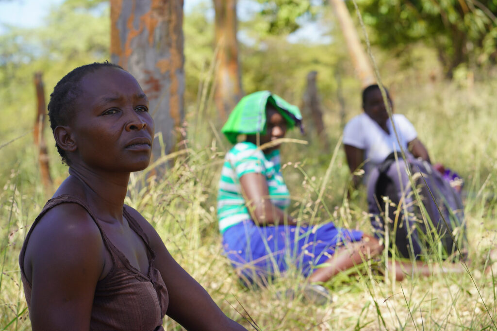 Women sit in the grass while socially distancing during Coronavirus