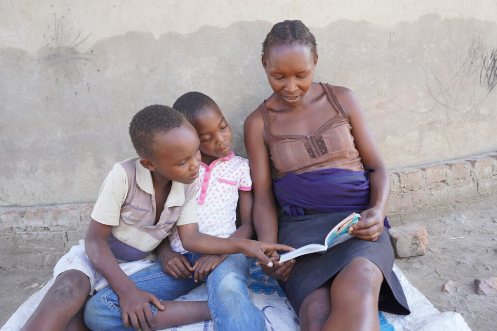 Rebecca Kapaira reads to two of her children outside of their home.
