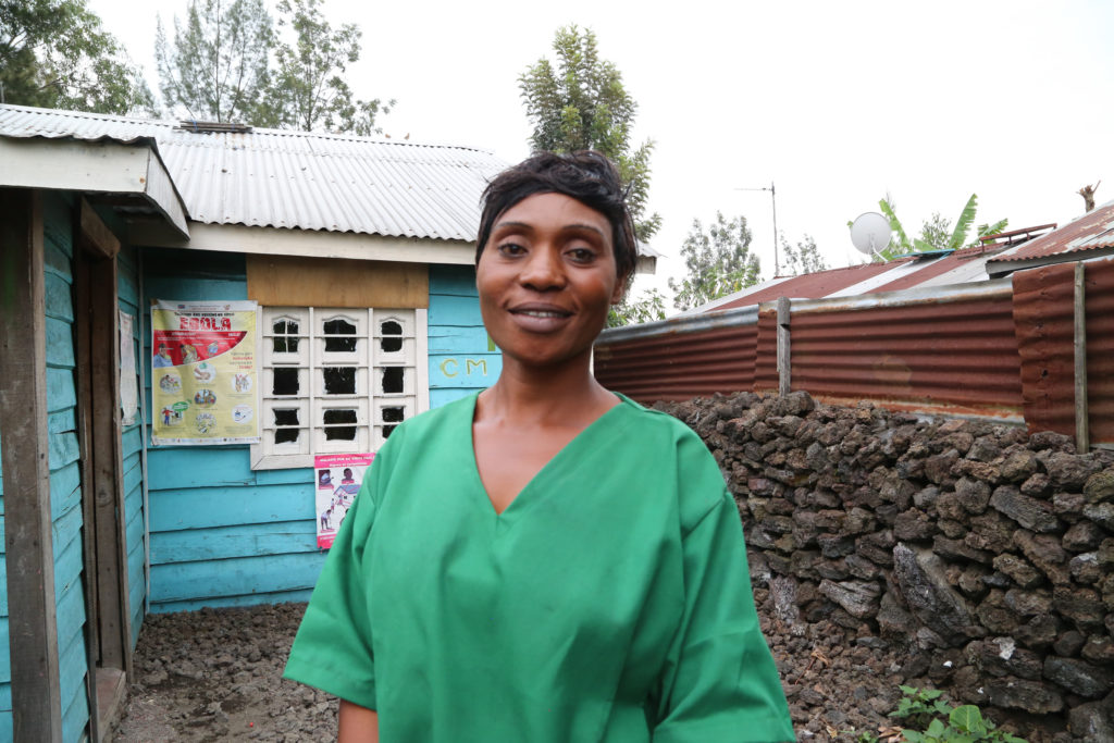 A nurse in green scrubs is pictured standing outside her house, smiling