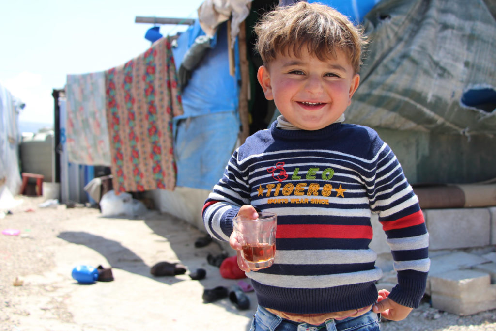 A young boy stands outside wearing a sweater, smiling, holding a cup of tea.