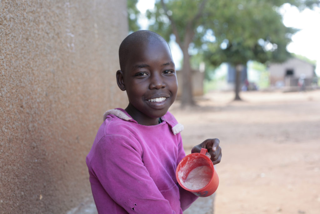 A young girl in Uganda wearing purple smiles for a camera