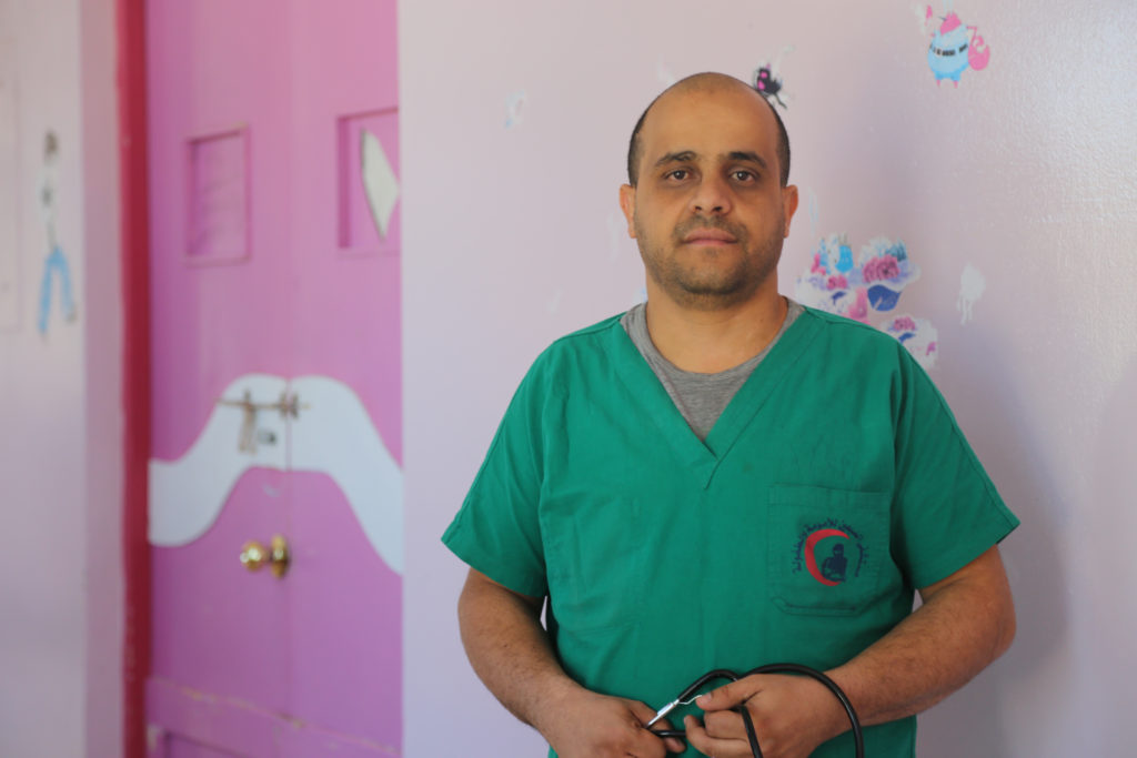 A nurse in green scrubs stands in front of a pink wall