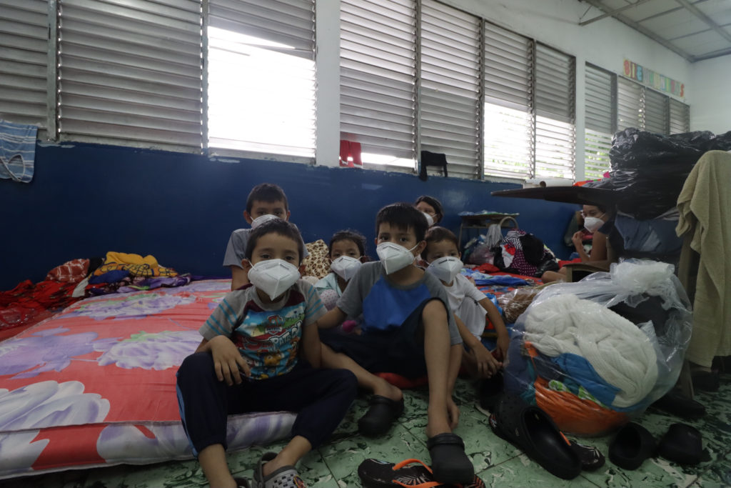 masked children sitting on mattresses on the floor