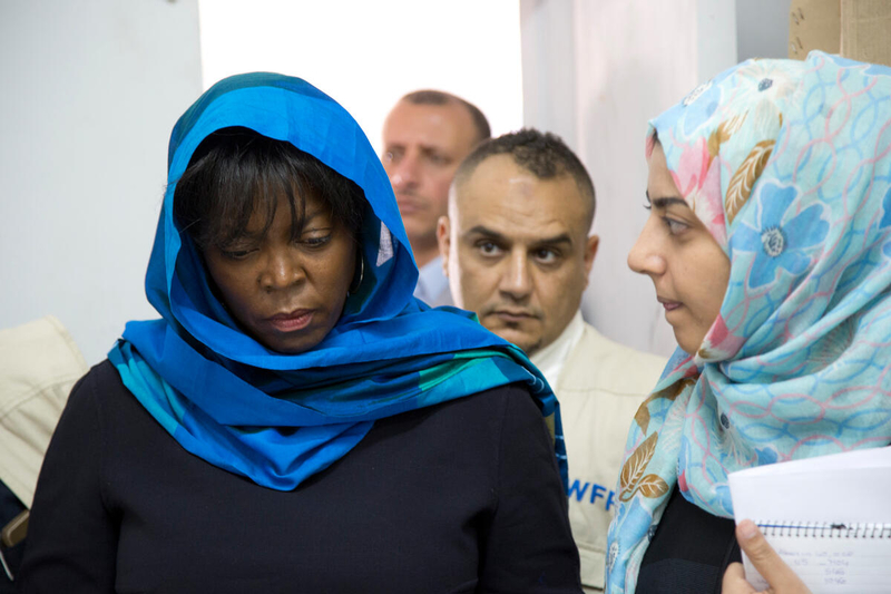 woman in blue headscarf walking with head down