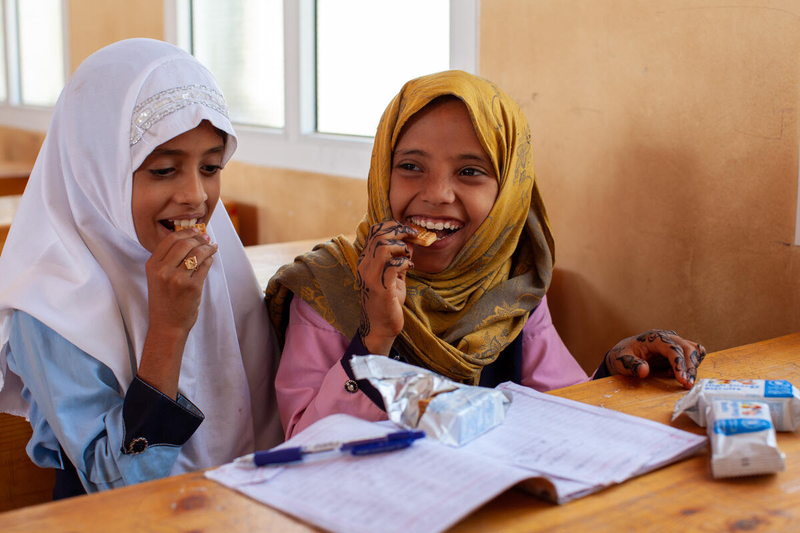 two schoolgirls smile while snacking