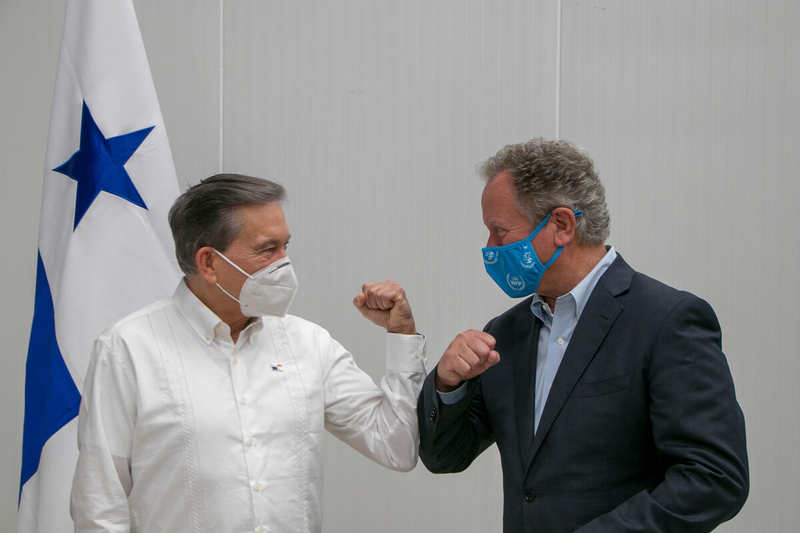 men taps elbows while wearing COVID-19 health masks