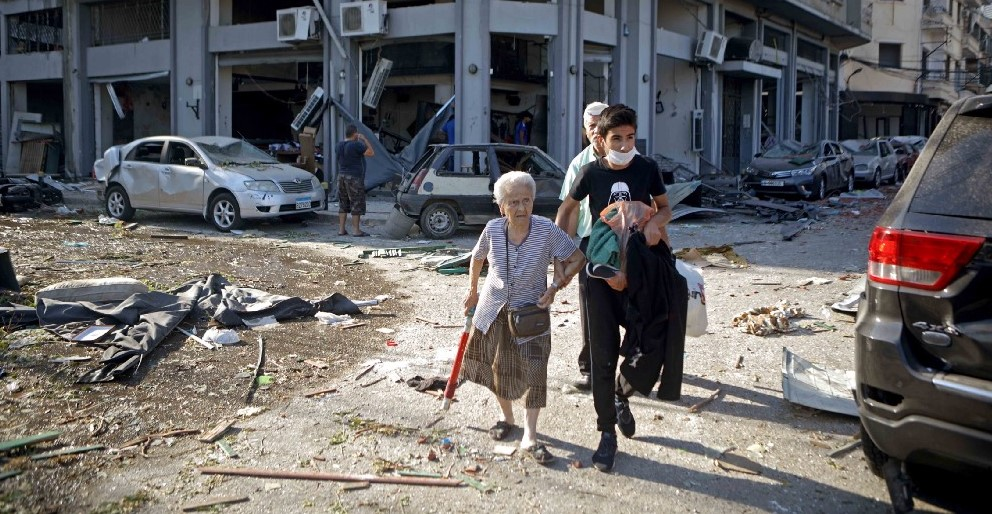 A family walks away from destroyed buildings.