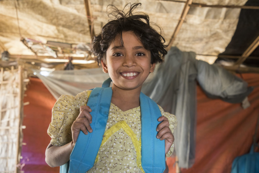 A young girl standing in a tent in a yellow backpack smiles at the camera