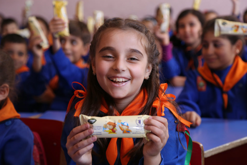 A young girl in a school uniform holds a wrapped bar up to the camera, smiling.