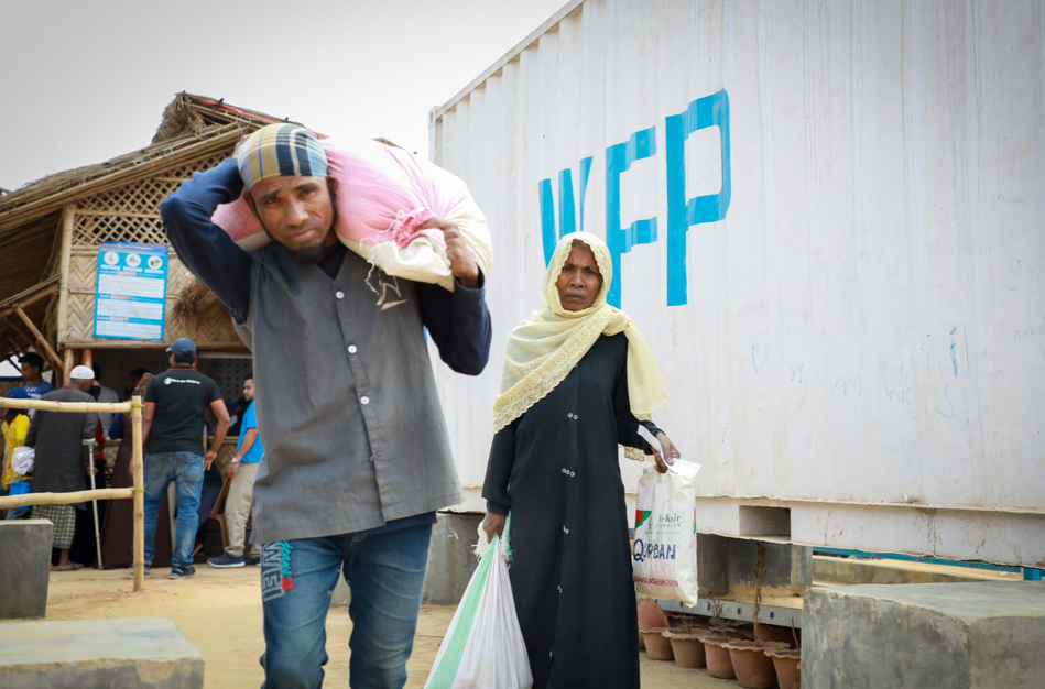 A man and woman walk towards the camera holding rations of food.