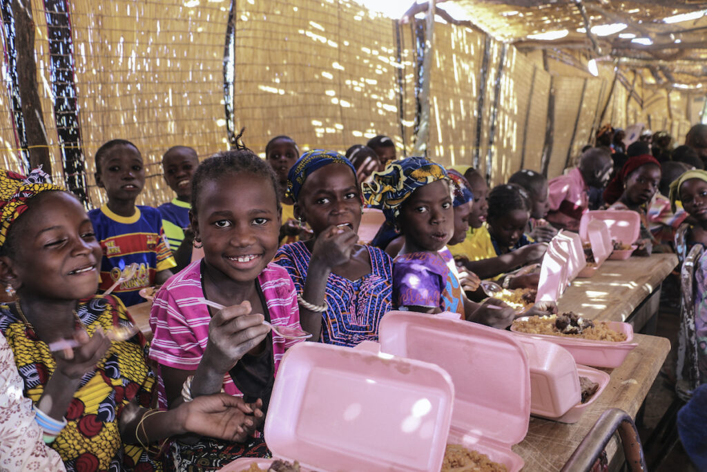 School children sit in rows at tables, holding pink boxes of food