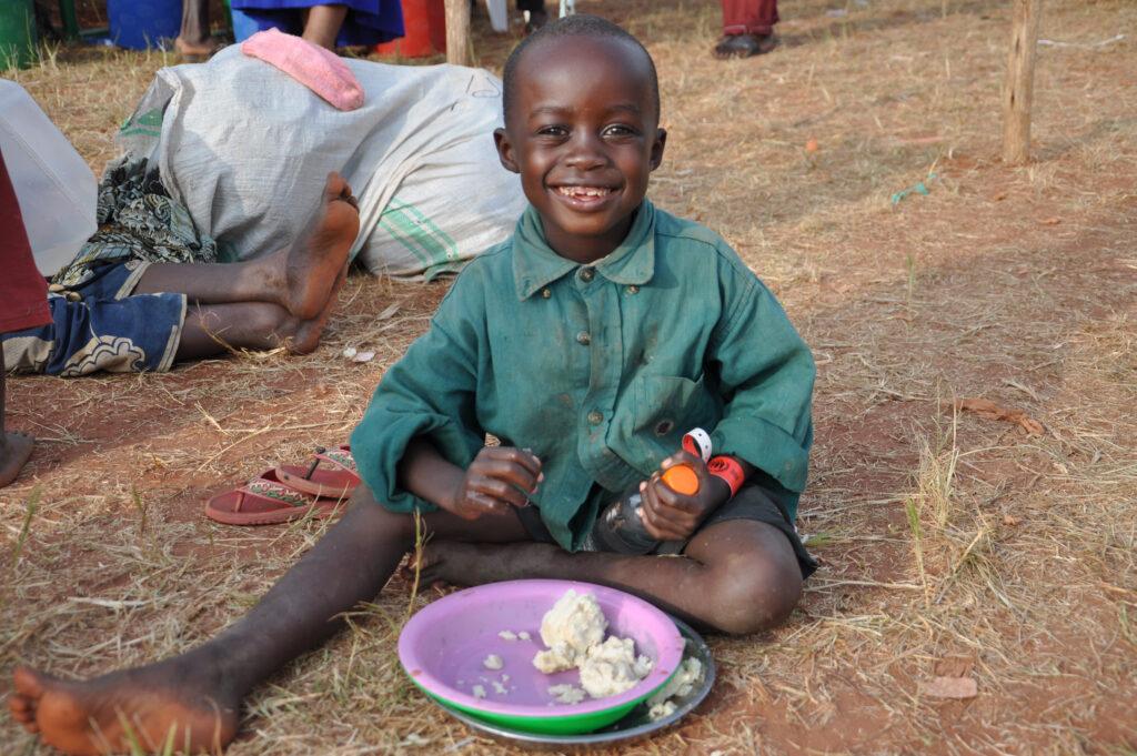 a young boy eats porridge while smiling