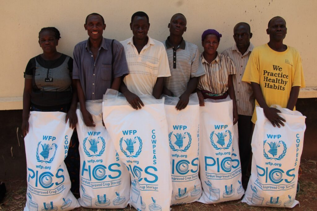 7 people stand in a line holding WFP grain storage bags in front of them