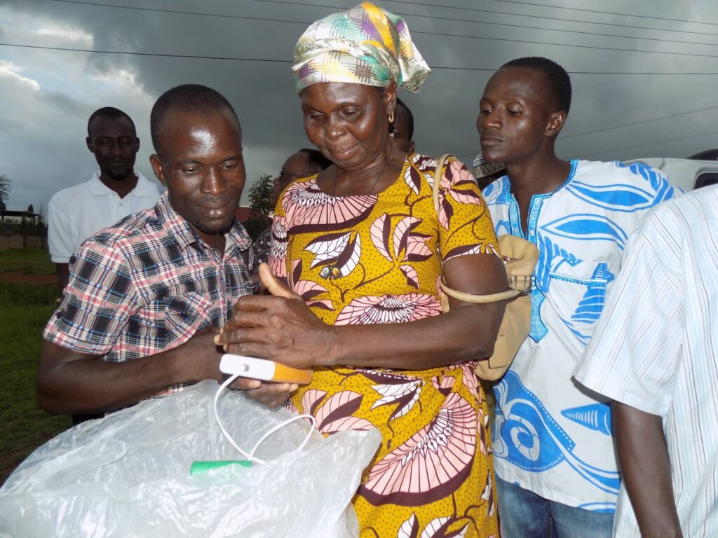 A woman flanked by two men look down at a meter connected by wire to a bag of grain.