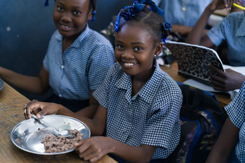 Two young girls in school uniforms enjoy a school meal.