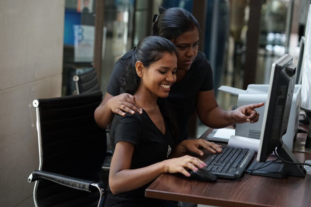 Two young women in black t-shirts work together at a computer.