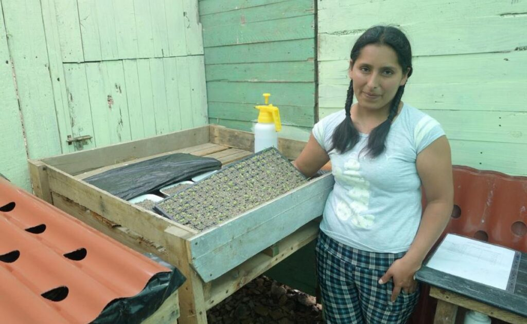 A young woman stands next to hydroponic supplies.