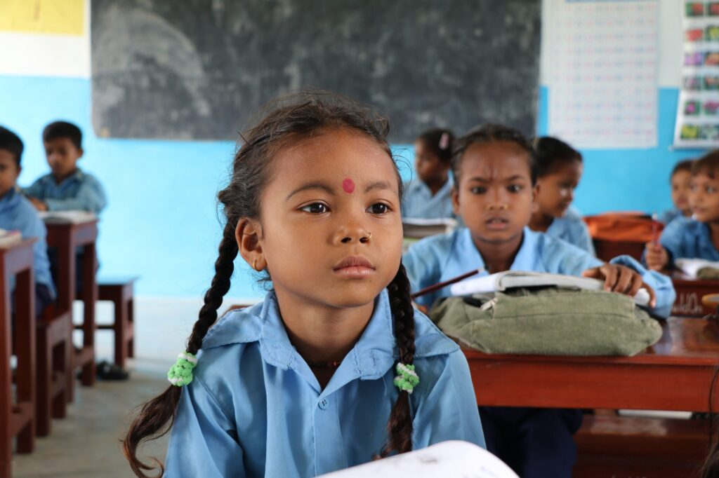 A young girl in a school uniform sits at a school desk in a classroom.