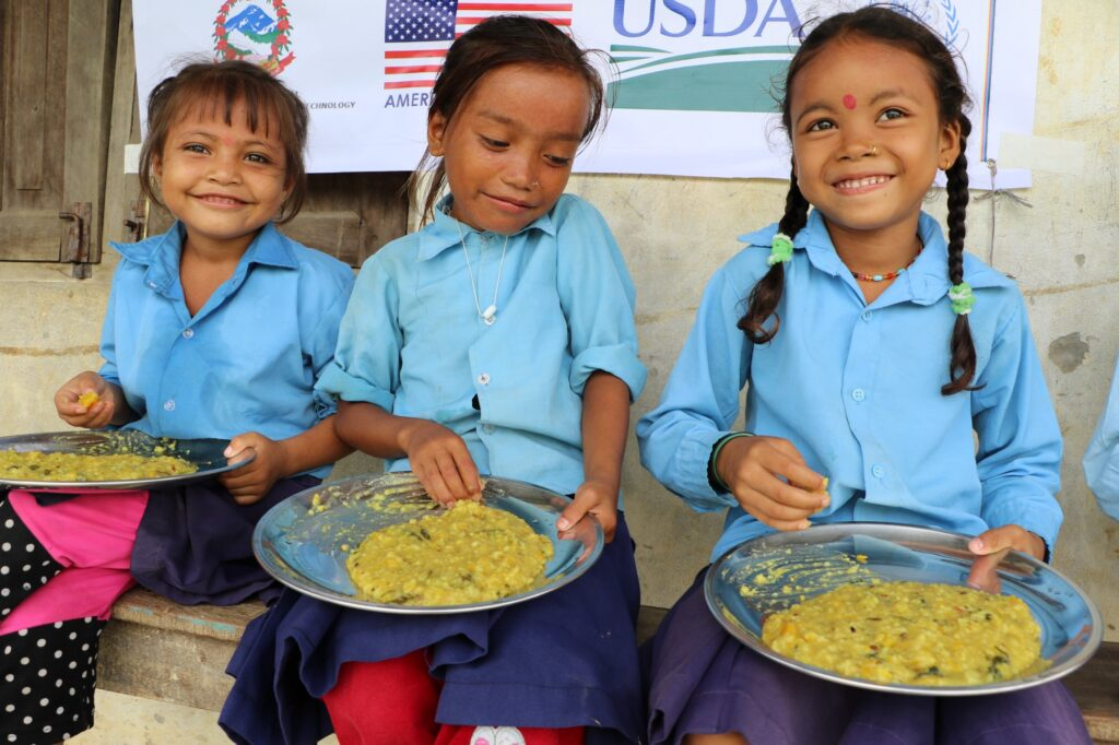 Three girls in school uniforms eat from plates of food in their laps, smiling.