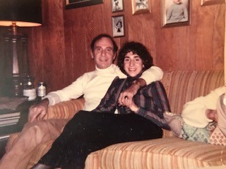 A young woman sits on a couch next to her father, his arm around her.