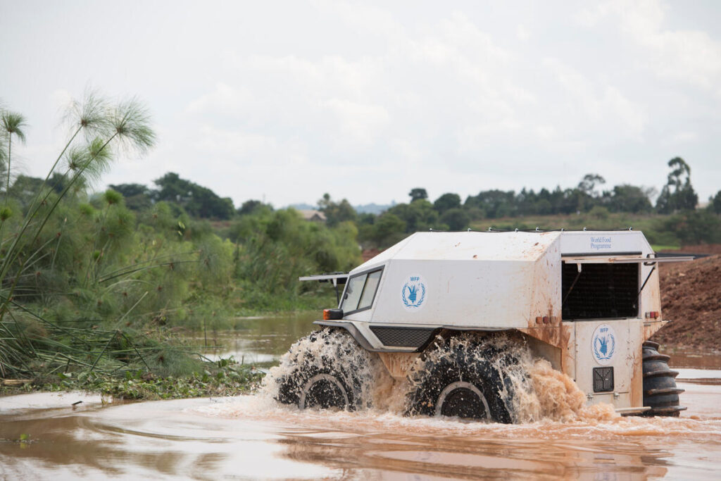 A SHERP vehicle drives across a muddy river.
