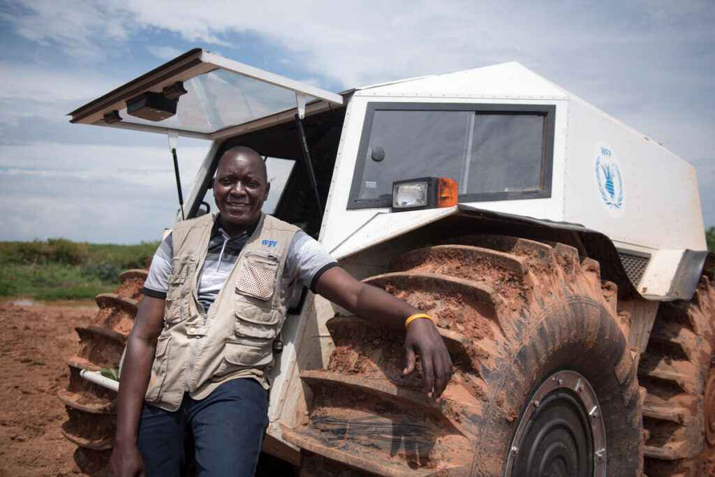 A WFP driver in a vest stands in front of a SHERP vehicle.