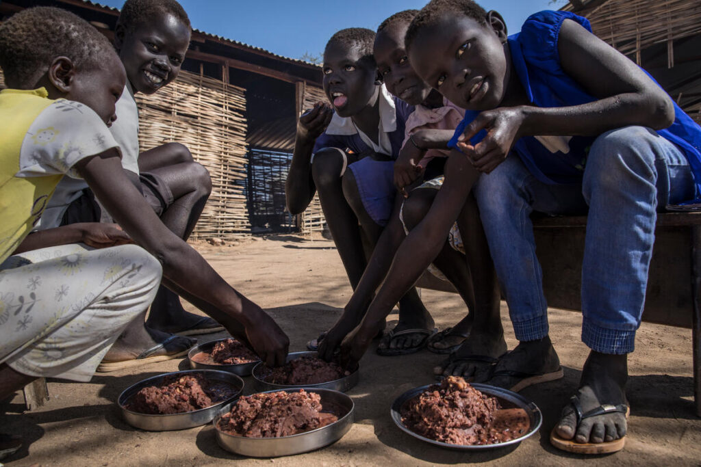 Kids sit outside, leaning over a shared plate of food.