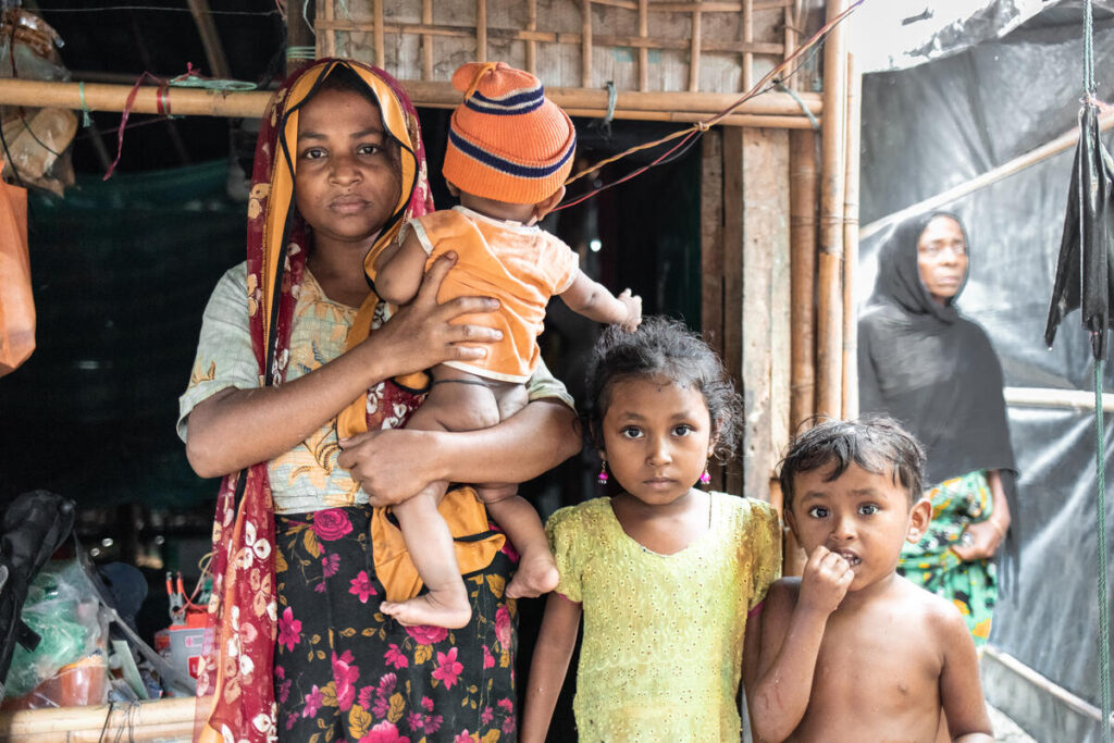 A mother holds her baby, looking at the camera, with her two young children standing next to her.