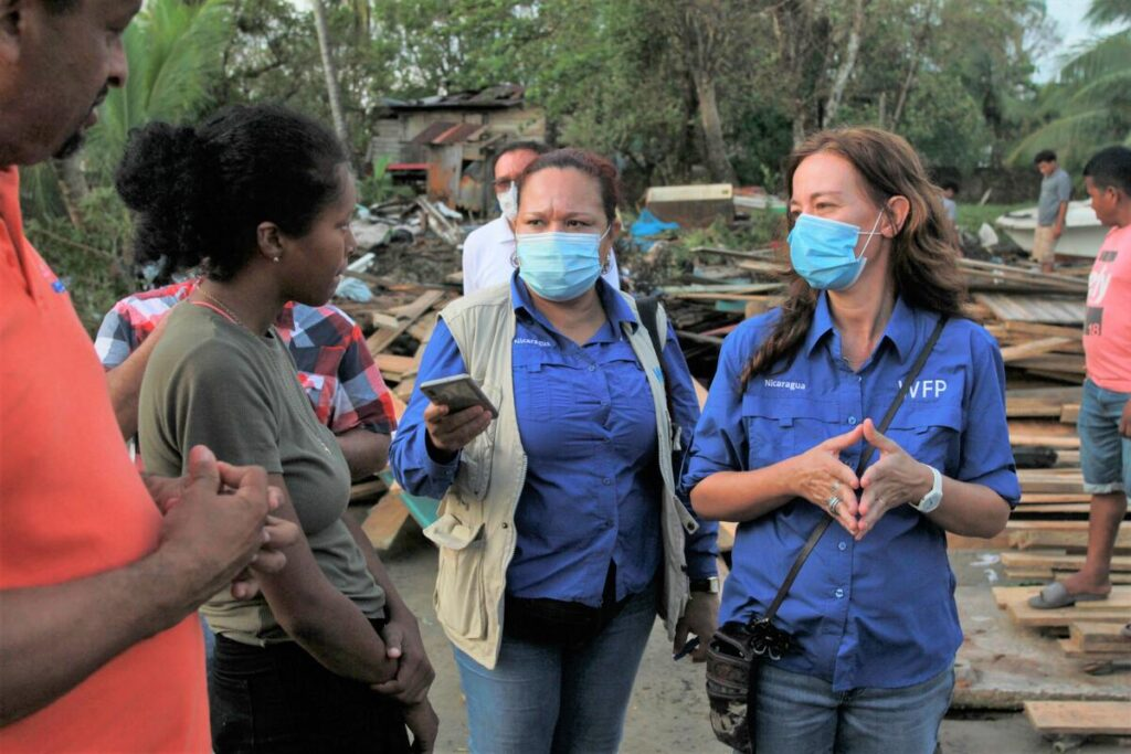 WFP workers in masks talk to a man and woman, surrounded by hurricane rubble.
