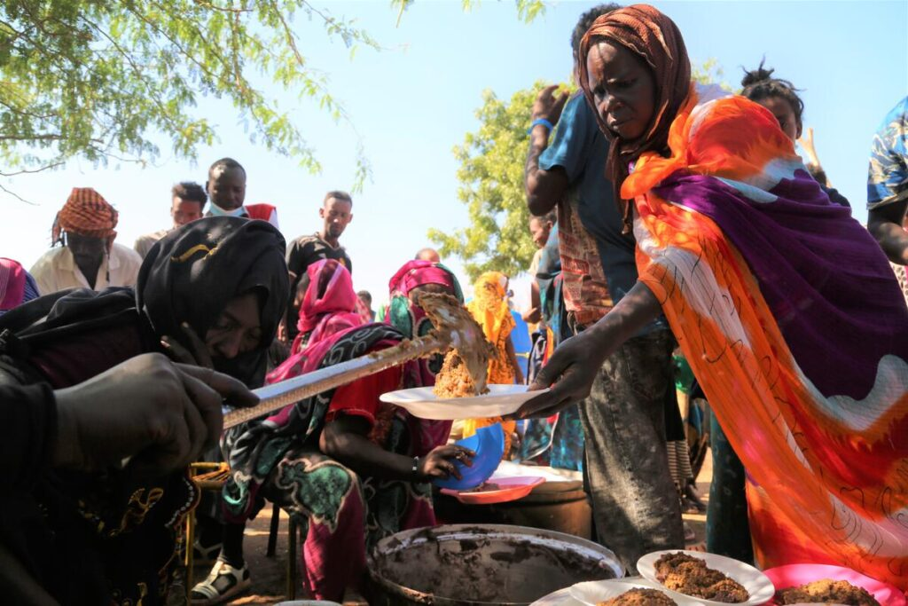 A woman holds out a plate, and volunteers serve her food from plates on the ground.