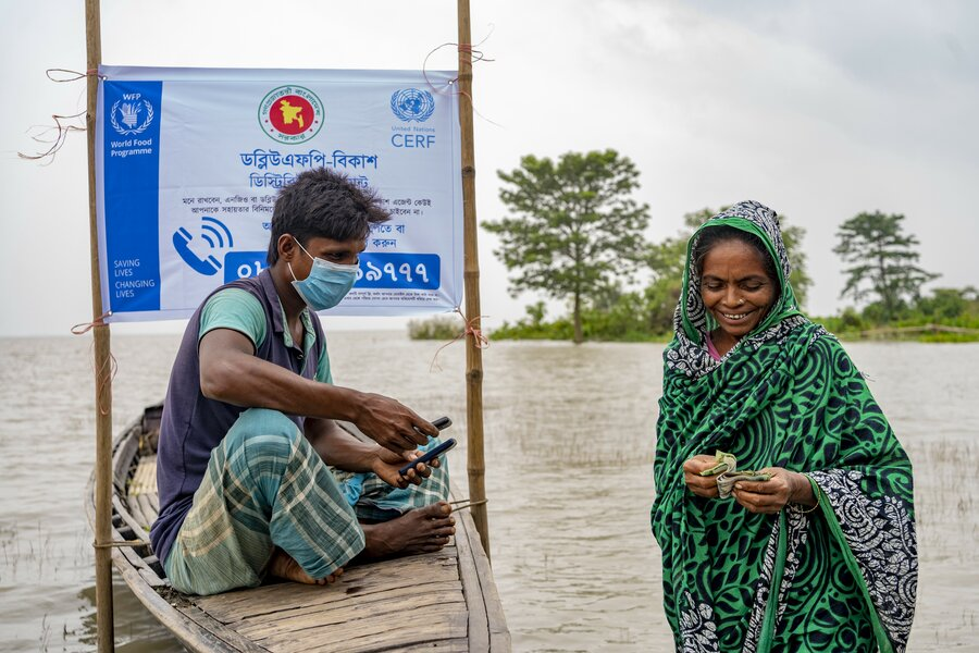 Woman smiling and holding money standing next to a man on a wooden boat with WFP sign above him. Water surrounds them.