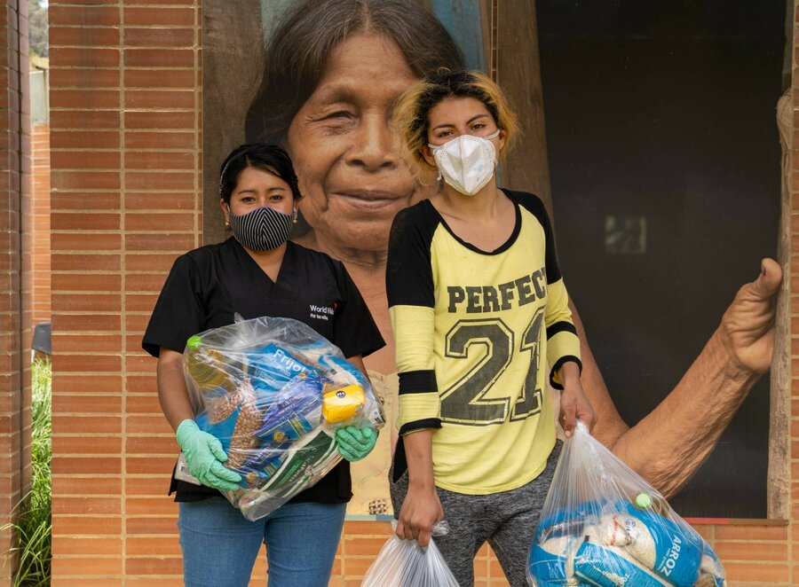Two women wearing medical masks and holding bags of food are standing and looking at camera.