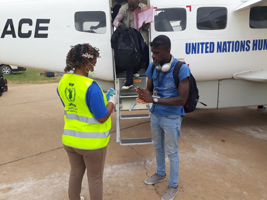 Two humanitarian aid workers standing next to a plane. WFP worker is looking at ticket.