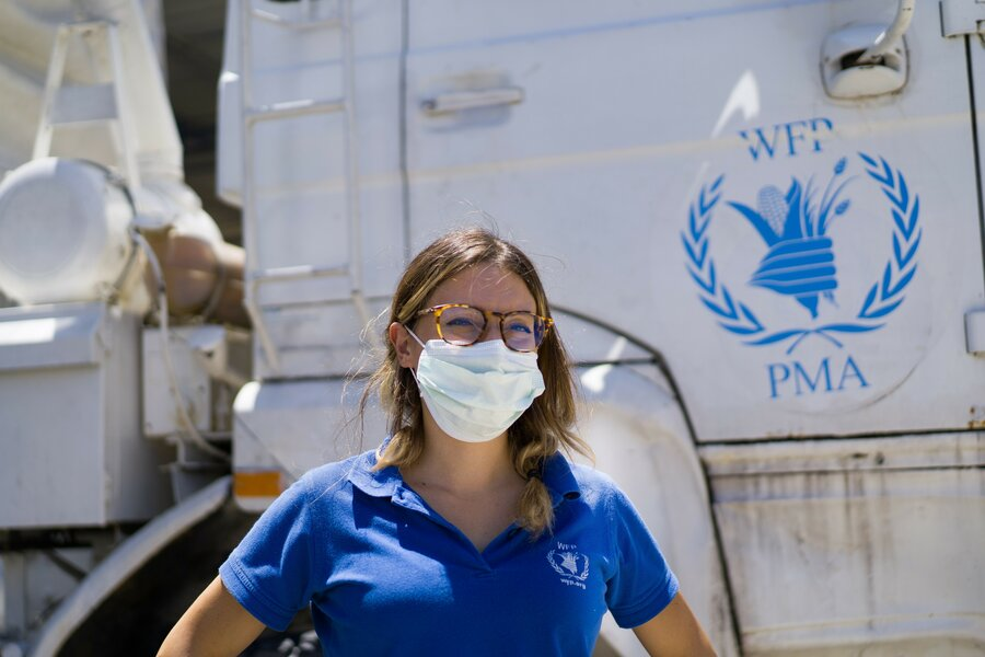 Woman wearing medical mask standing in front of WFP truck.