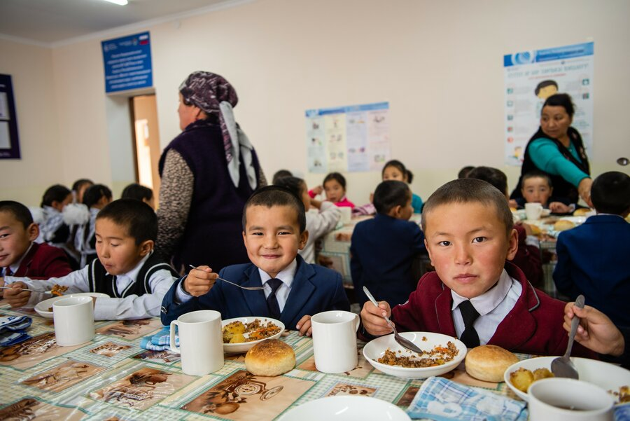 Children in a school cafeteria. Two boys are feeding and looking at the camera.